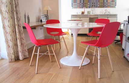 Red Ooland chairs around a white Trumpet dining table